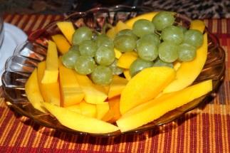 Zum Vespern eine Tasse heißen Kaffee und ein Fruchtteller mit Mango-Scheiben und Weintrauben.